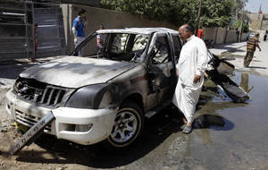 Photo - Civilians inspect the aftermath of a car bomb attack in Baghdad, Iraq, Wednesday, July 24, 2013. A bomb exploded near a Sunni mosque in Baghdad's southern Dora neighborhood on Tuesday killing several people and wounding many, police said. (AP Photo/Karim Kadim)