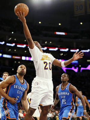 Photo - Los Angeles Lakers guard Jodie Meeks makes a reverse layup in front of Oklahoma City Thunder guard Derek Fisher, left, and guard Reggie Jackson during the second half of an NBA basketball game in Los Angeles, Sunday, March 9, 2014. The Lakers won 114-110, with Meeks scoring a career-high 42 points. (AP Photo/Danny Moloshok)