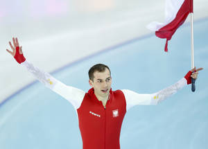 Photo - Gold medallist Poland's Zbigniew Brodka holds his national flag and celebrates after the men's 1,500-meter speedskating race at the Adler Arena Skating Center during the 2014 Winter Olympics in in Sochi, Russia, Saturday, Feb. 15, 2014. (AP Photo/Pavel Golovkin)