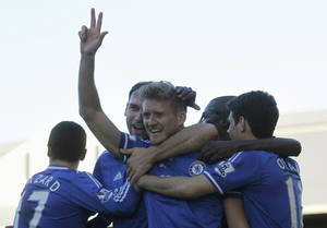 Photo - Chelsea's Andre Schurrle, center, celebrates his third goal against Fulham with teammates during their English Premier League soccer match at Craven Cottage, London, Saturday, March 1, 2014. (AP Photo/Sang Tan)