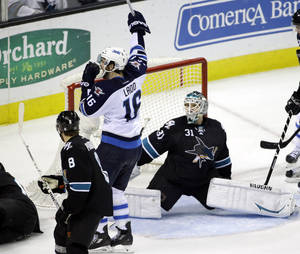 Photo - Winnipeg Jets' Andrew Ladd (16) celebrates a goal by teammate Tobias Enstrom, not pictured, next to San Jose Sharks goalie Antti Niemi (31), of Finland, during the third period of an NHL hockey game on Thursday, March 27, 2014, in San Jose, Calif.  Winnipeg won 4-3. AP Photo/Marcio Jose Sanchez)