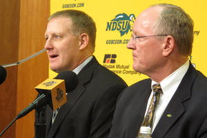 Photo - North Dakota State defensive coorindator Chris Klieman, left, and athletic director Gene Taylor talk about Klieman's promotion to head coach during a news conference Sunday, Dec. 15, 2013 in Fargo, N.D. (AP Photo/Dave Kolpack)