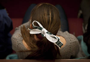 photo - A young woman wears a green and white bow, the colors of Sandy Hook Elementary School, in her hair with the initials of the victims names from the Dec. 14, 2012 shooting during an interfaith a sermon at Newtown Congregational Church in Newtown, Conn., Sunday, Jan. 20, 2013.  The Rev. James A. Forbes, Jr., who led one of the country's most prominent liberal Protestant churches, is speaking at the church to honor the victims of last month's school shooting and the legacy of the Rev. Martin Luther King Jr. (AP Photo/Jessica Hill)