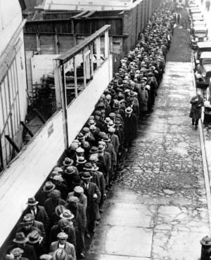 Photo - In this 1932 file photo, long line of jobless and homeless men wait outside to get free dinner at New York's municipal lodging house during the  Great  Depression. (AP File Photo)