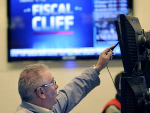 """Photo -   FILE - In this Nov. 7, 2012, file photo, James Dresch of MND Partners Inc. works on the floor of the New York Stock Exchange in New York. Wall Street also appeared headed for gains on the open Wednesday Nov. 14, 2012 as renewed efforts got under way in Washington to resolve the impending """"fiscal cliff."""" (AP Photo/Henny Ray Abrams, File)"""