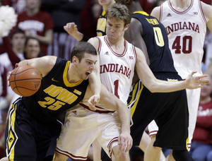 Photo - Iowa forward Eric May is fouled by Indiana guard Jordan Hulls as they get tangled up in the second half of an NCAA college basketball game in Bloomington, Ind., Saturday, March 2, 2013. Indiana defeated Iowa 73-60. (AP Photo/Michael Conroy)