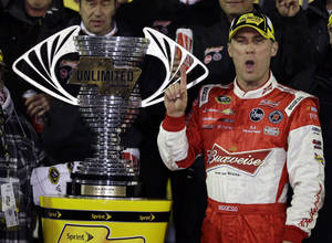 photo - Kevin Harvick stands in Victory Lane next to the championship trophy after winning the NASCAR Sprint Unlimited auto race at Daytona International Speedway, Saturday, Feb. 16, 2013, in Daytona Beach, Fla.(AP Photo/John Raoux)