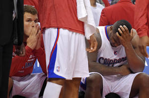 Photo - Los Angeles Clippers' Blake Griffin, left, looks on from the bench as Glen Davis rubs his head during the second half in Game 1 of an opening-round NBA basketball playoff series, Saturday, April 19, 2014, in Los Angeles. The Warriors won 109-105. (AP Photo/Mark J. Terrill)