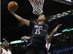 Photo - Minnesota Timberwolves guard Kevin Martin (23) shoots in front of Oklahoma City Thunder center Kendrick Perkins, left, and forward Serge Ibaka, right, during the first quarter of an NBA basketball game in Oklahoma City, Wednesday, Feb. 5, 2014. (AP Photo/Sue Ogrocki)
