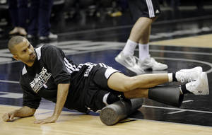 Photo - San Antonio Spurs' Tony Parker uses a foam roller to workout with during NBA basketball practice, Saturday, June 15, 2013, in San Antonio. The Spurs host the Miami Heat in Game 5 of the NBA Finals on Sunday, with the best-of-seven games series even at 2-2. (AP Photo/David J. Phillip)