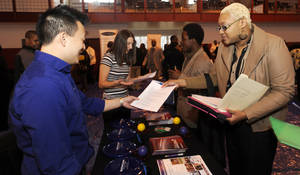 Photo - Luke Gill, left, of Quicken Loans, talks with job candidate Jasmine Boykins at a job fair at the Matrix Center in Detroit.   AP Photo <strong>David Coates -  AP </strong>