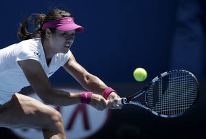 Photo - Li Na of China hits a backhand return to Lucie Safarova of the Czech Republic during their third round match at the Australian Open tennis championship in Melbourne, Australia, Friday, Jan. 17, 2014.(AP Photo/Rick Rycroft)