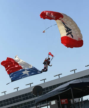 Photo -   A parachute jumper carrying the Texas state flag descends on the track before the NASCAR Sprint Cup Series auto race at Texas Motor Speedway, Sunday, Nov. 4, 2012, in Fort Worth, Texas. The weight used to balance the flag fell into Kevin Harvick's No. 29 car. (AP Photo/The Fort Worth Star-Telegram, Rodger Mallison) MAGS OUT; (FORT WORTH WEEKLY, 360 WEST)