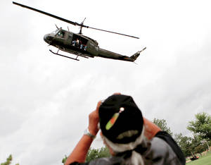 Photo - A Vietnam veteran takes a photo of a Huey helicopter Sunday as it flies over Reaves Park in Norman.