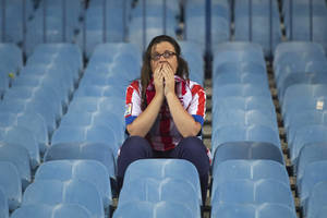 Photo - An Atletico supporter reacts after the team lost the Champions League final soccer match, taking place in Portugal, between Real Madrid and Atletico Madrid, in Madrid, Spain, Saturday, May 24, 2014. (AP Photo/Gabriel Pecot)