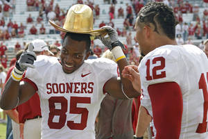 Photo - CELEBRATION: Oklahoma's Ryan Broyles (85) and Travis Lewis (12) celebrate with the Golden Hat trophy after the Sooners 55-17 win over Texas during the Red River Rivalry college football game between the University of Oklahoma Sooners (OU) and the University of Texas Longhorns (UT) at the Cotton Bowl in Dallas, Saturday, Oct. 8, 2011. Photo by Chris Landsberger, The Oklahoman  ORG XMIT: KOD