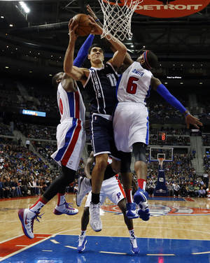 Photo - Thunder center Steven Adams, center, drives between Pistons forward Greg Monroe, left, and forward Josh Smith in the second half Friday in Detroit. AP photo