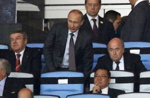 Photo - Russian President Vladimir Putin, standing, is flanked by IOC president Thomas Bach, left, and FIFA President Sepp Blatter while watching the World Cup final soccer match between Germany and Argentina at the Maracana Stadium in Rio de Janeiro, Brazil, Sunday, July 13, 2014. (AP Photo/Frank Augstein)