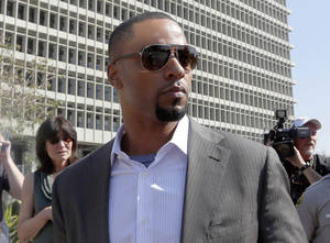Photo - In this Feb. 14, 2014, photo, former NFL safety Darren Sharper leaves a courthouse in Los Angeles. An arrest warrant has been issued for Sharper and another man, accusing them of raping two women in New Orleans last year. Sharper also is under investigation in sexual assault cases in Florida, Nevada and Arizona and has pleaded not guilty to rape charges in Los Angeles. (AP Photo/Nick Ut )