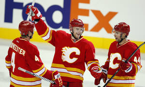 photo - Calgary Flames' Matt Stajan, center, celebrate his second goal with teammates Jay Bouwmeester, left, and Chris Butler during the third period of an NHL hockey game against the Minnesota Wild in Calgary, Alberta, Saturday, Feb. 23, 2013. (AP Photo/The Canadian Press, Jeff McIntosh)