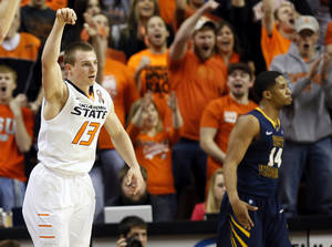photo - Oklahoma State&#039;s Phil Forte (13) reacts in front of West Virginia&#039;s Gary Browne (14) after hitting a 3-point shot during an NCAA men&#039;s basketball game between Oklahoma State University (OSU) and West Virginia at Gallagher-Iba Arena in Stillwater, Okla., Saturday, Jan. 26, 2013. Photo by Nate Billings, The Oklahoman