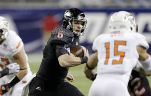 Photo - Northern Illinois quarterback Jordan Lynch scrambles through the Bowling Green defense during the first quarter of an NCAA college football game at the Mid-American Conference championship in Detroit, Friday, Dec. 6, 2013. (AP Photo/Carlos Osorio)