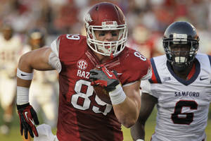 Photo - Arkansas tight end Mitchell Loewen (89) runs into the end zone ahead of Samford defensive back Jaquiski Tartt (6) during the first quarter of an NCAA college football game in Little Rock, Ark., Saturday, Sept. 7, 2013. (AP Photo/Danny Johnston)