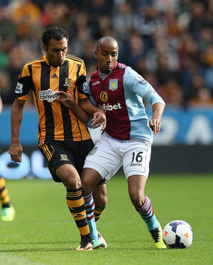Photo - Aston Villa's Fabian Delph, right, and Hull City's Ahmed Elmohamady battle for the ball during the English Premier League soccer match at the KC Stadium, Hull, England, Saturday Oct. 5, 2013. (AP Photo/PA, Lynne Cameron) UNITED KINGDOM OUT