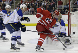 Photo - Carolina Hurricanes' Jiri Tlusty, second from right, of the Czech Republic, tries to score against St. Louis Blues goalie Jaroslav Halak (41) as Jay Bouwmeester (19) defends during the second period of an NHL hockey game in Raleigh, N.C., Friday, Jan. 31, 2014. (AP Photo/Gerry Broome)