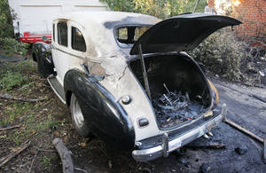Photo - A burned 1941 Hudson sits in the driveway at the scene of a house fire.  Photo by Paul B. Southerland, The Oklahoman
