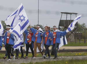 Photo - Young jewish people from Israel and other countries march in silence between the two parts of Auschwitz-Birkenau, the Nazi German death camp, in an annual march of the living in Oswiecim, Poland, on Monday, April 28, 2014, which is held in memory of some 6 million Jews killed during the Holocaust. This year, the march honors some 430,000 Hungarian Jews killed in Birkenau gas chambers in 1944. (AP Photo/Czarek Sokolowski)