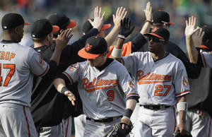 Photo -   Baltimore Orioles, including Nate McLouth (9) and Endy Chavez (27), celebrate at the end of a baseball game against the Oakland Athletics, Sunday, Sept. 16, 2012, in Oakland, Calif. The Orioles won 9-5.(AP Photo/Ben Margot)