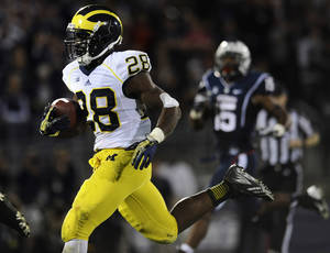 Photo - Michigan running back Fitzgerald Toussaint (28) runs for 35 yards to score a touchdown during the second half of an NCAA college football game against Connecticut at Rentschler Field, Saturday, Sept., 21, 2013, in East Hartford, Conn. (AP Photo/Jessica Hill)