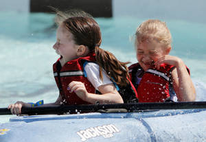 Photo - Claire Foreman, 7, front, and Paige Hesse, 7, are splashed with water while kayaking during the Festival of the Child at Yukon City Park on Saturday. Photos by Nate Billings, The Oklahoman