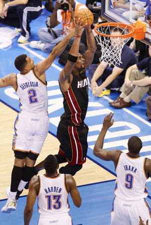 Photo - Miami's Chris Bosh, right, dunks the ball against Oklahoma City's Thabo Sefolosha, left, James Harden and Serge Ibaka in the fourth quarter during Game 2 of the NBA Finals at Chesapeake Energy Arena on Thursday. Miami won, 100-96. Photo by Nate Billings, The Oklahoman