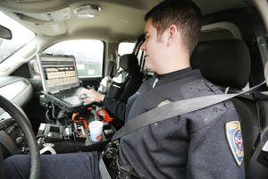 photo - Edmond police officer Paul Phillips works on a report using his laptop computer in his car in front of Orvis Risner Elementary School.  PHOTO BY STEVE GOOCH, THE OKLAHOMAN