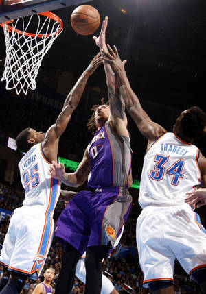 Photo - Phoenix's Michael Beasley (0) shoots in between Oklahoma City's DeAndre Liggins (25) and Hasheem Thabeet (34) during the NBA game between the Oklahoma City Thunder and the Phoenix Suns at the Chesapeake Energy Arena, Friday, Feb. 8, 2013.Photo by Sarah Phipps, The Oklahoman