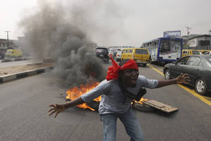 "Photo - FILE- An unidentified man shouts slogans near burning tyres during a protest on a major road junction in the commercial capital of Lagos, Nigeria, during a fuel subsidy protest in this file photo dated Tuesday, Jan. 3, 2012, as angry mobs call on the government to keep a cherished consumer subsidy that had kept gas affordable for more than two decades. A 30-minute film documentary called ""Fuelling Poverty"" has been online for months, but it is revealed Sunday April 21, 2013, that Nigerian officials have refused its director Ishaya Bako permission to show it publicly in this oil-rich nation, as it focuses on the January 2012 protests and the alleged billions of dollars thought to have been swallowed up by greedy companies and the nation's elite.(AP Photo/Sunday Alamba, FILE)"