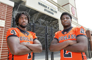 Photo - Douglass High School defensive ends D.J. Ward, left, and Deondre Clark stand in front of the gate of Moses F. Miller Stadium at Douglass High School inOklahoma City, OK, Friday, August 17, 2012,  By Paul Hellstern, The Oklahoman <strong>PAUL HELLSTERN - Oklahoman</strong>