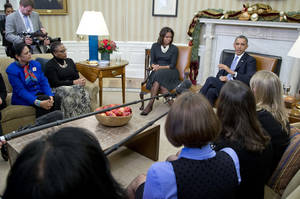 Photo - President Barack Obama gestures as he speaks to the media as he and first lady Michelle Obama meet with a group of mothers in the Oval Office of the White House in Washington, Wednesday, Dec. 18, 2013, to discuss how health care reform could benefit their families. (AP Photo/Carolyn Kaster)