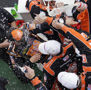Photo -   Joey Logano, left, is celebrates with crew members after winning NASCAR's Sprint Cup Series Pocono 400 auto race on Sunday, June 10, 2012, in Long Pond, Pa. (AP Photo/Matt Slocum)