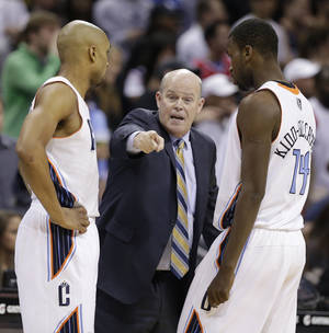 Photo - Charlotte Bobcats head coach Steve Clifford, center, talks with Gerald Henderson, left, and Michael Kidd-Gilchrist, right, during the second half of an NBA basketball game against the Washington Wizards in Charlotte, N.C., Monday, March 31, 2014. The Bobcats won 100-94. (AP Photo/Chuck Burton)