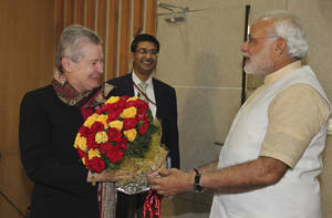 Photo - In this photo released by India's Gujarat state government, U.S. Ambassador to India, Nancy Powell, left, receives flowers presented to her by India's opposition Bharatiya Janata Party's prime ministerial candidate Narendra Modi, right, as she visits him at his residence in Gandhinagar, India, on Feb. 13, 2014. Powell met with the Gujarat chief minister for the first time since he was refused a U.S. visa over alleged complicity in deadly anti-Muslim riots in 2002. Indian election results due Friday, May 16 provide a chance to repair relations with the U.S. that were strained by the arrest of an Indian diplomat in New York. But there's a big catch: Washington's uneasy relationship with Modi, the man expected to become India's next prime minister.  (AP Photo/Gujarat state government)