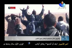 photo - In this image made from video, a group of people believed to be hostages kneel in the sand with their hands in the air at an unknown location in Algeria. Algerian de-mining teams were scouring a gas refinery on Sunday, Jan. 20, 2013 that was the scene of a bloody four-day standoff, searching for explosive traps left by the Islamist militants who took dozens of foreigners hostage. The siege left at least 23 captives dead, and the American government warned that there were credible threats of more kidnapping attempts on Westerners. (AP Photo/Ennahar TV) ALGERIA OUT, TV OUT