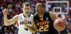 Photo - Oklahoma State's Markel Brown (22) tries to get past Gonzaga's Kevin Pangos (4) during a second round game of the NCAA men's college basketball tournament at Viejas Arena in San Diego, between Oklahoma State and Gonzaga Friday, March 21, 2014. Photo by Bryan Terry, The Oklahoman