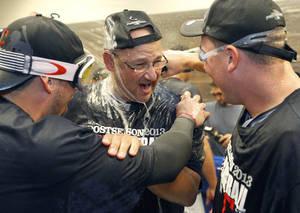 Photo - Cleveland Indians manager Terry Francona, center, is sprayed with champagne in the locker room after the Indians beat the Twins 5-1 in a baseball game in Minneapolis, Sunday, Sept. 29, 2013,  to clinch a wild card spot in the playoffs. (AP Photo/Ann Heisenfel
