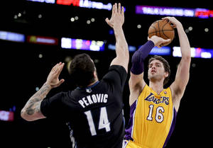 Photo - Los Angeles Lakers center Pau Gasol shoots over Minnesota Timberwolves center Nikola Pekovic during the first half of an NBA basketball game in Los Angeles, Friday, Dec. 20, 2013. (AP Photo/Chris Carlson)