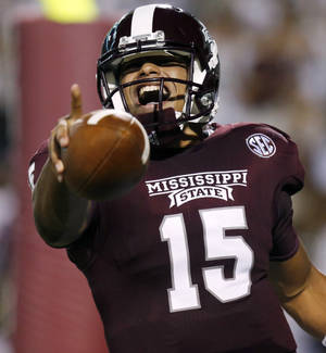 Photo - Mississippi State quarterback Dak Prescott (15) celebrates his second quarter touchdown run against Troy in their NCAA college football game at Davis Wade Stadium in Starkville, Miss., on Saturday, Sept. 21, 2013. (AP Photo/Rogelio V. Solis)