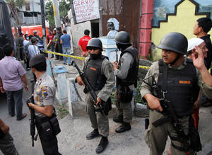 Photo -   Indonesian police officers stand guard outside a building after a raid in Solo, Central Java, Indonesia, Saturday, Oct. 27, 2012. Indonesian police say they have arrested 11 people suspected of planning a range of terrorist attacks on domestic and foreign targets including the U.S. and Australian embassies. (AP Photo)