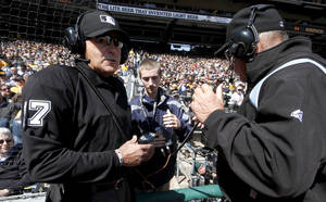 Photo - First base umpire Bob Davidson, right, and home plate umpire John Hirschbeck, left, talk over headsets as a play at first base is being reviewed in the fifth inning during the opening day baseball game between the Pittsburgh Pirates and the Chicago Cubs on Monday, March 31, 2014, in Pittsburgh. Chicago Cubs manager Rick Renteria requested a replay on an out call. (AP Photo/Gene Puskar)